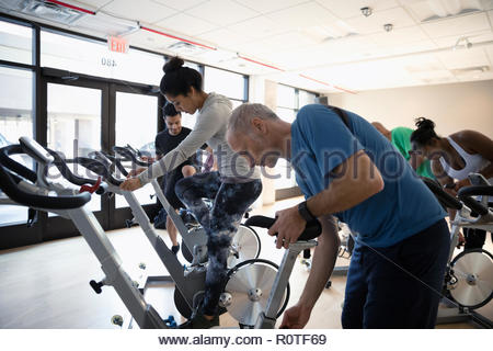 Man adjusting seat of exercise bike, preparing for spin class in gym - Stock Photo
