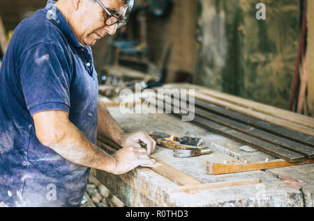 Professional carpenter sanding and restoring wooden surfaces. - Stock Photo