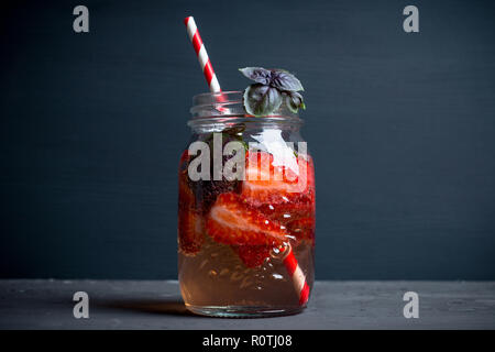 Fresh cocktail with strawberry and basil in glass. Shallow depth of field. - Stock Photo