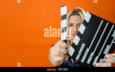 Woman holding in hand classic director clear empty black film making clapperboard - Stock Photo
