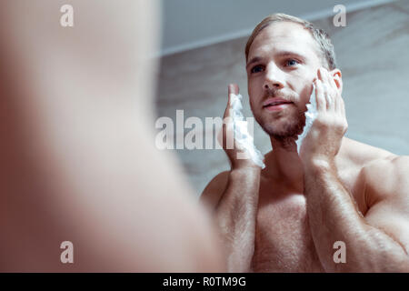 Blue-eyed man with nice muscle body shaving his face in the morning