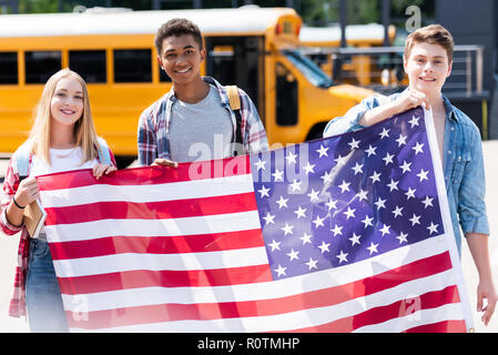 group of happy teen students holding usa flag in front of school bus - Stock Photo