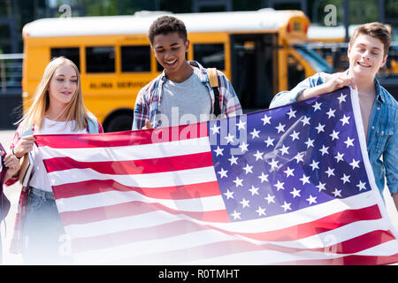 group of smiling teen students holding usa flag in front of school bus - Stock Photo