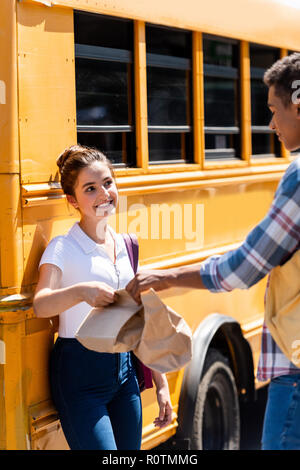 happy teen students holding paper bags with lunch while standing near school bus - Stock Photo