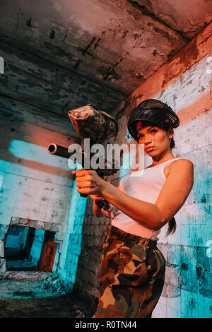 attractive young female paintballer in goggle mask above head aiming by paintball marker in abandoned building - Stock Photo