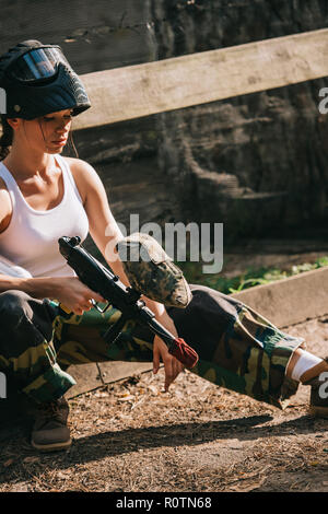 female paintballer in white singlet and goggle mask holding paintball gun outdoors - Stock Photo