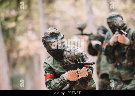 female paintballer in goggle mask and camouflage shooting by marker gun while her team running behind outdoors - Stock Photo