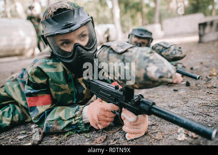 female paintball player in goggle mask and camouflage with marker gun crawling on ground outdoors - Stock Photo