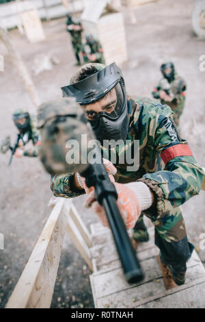 high angle view of male paintball player aiming by marker gun and running on staircase while his team standing behind outdoors - Stock Photo