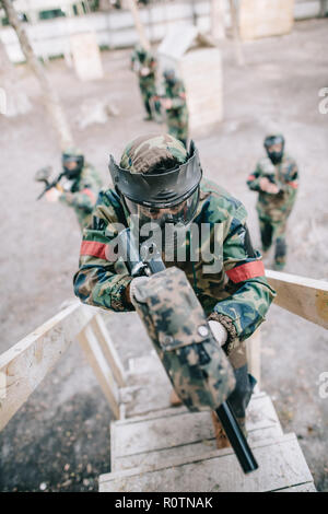 high angle view of paintball player aiming by marker gun and running on staircase while his team standing behind outdoors - Stock Photo