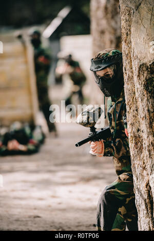 selective focus of female paintball player in goggle mask and camouflage aiming by paintball gun near tree outdoors - Stock Photo