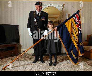 Mollie Stonelake, seven, holds a full-size standard from the Torpoint & District Branch of the Royal British Legion alongside branch chairman Colin Prideaux, in her family home in Torpoint, Cornwall. Mollie went on her first parade aged five and will carry a specially-made miniature standard in a service on Sunday in her home town of Torpoint in Cornwall. - Stock Photo