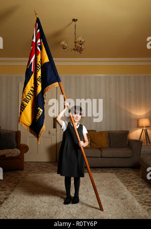 Mollie Stonelake, seven, holds a full-size standard from the Torpoint & District Branch of the Royal British Legion in her family home in Torpoint, Cornwall. Mollie went on her first parade aged five and will carry a specially-made miniature standard in a service on Sunday in her home town of Torpoint in Cornwall. - Stock Photo