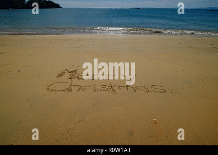 A sand message, Merry Christmas, hand written in the sand with the blue sea behind - Stock Photo