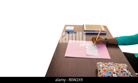 An African woman writes a check with a wooden pen in an office with a white background on a business table with a colourful, glittering purse. - Stock Photo