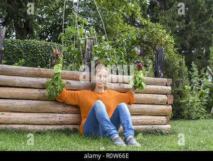 Junge Frau im Garten, erntet Karotten und Radieschen (model-released) - Stock Photo