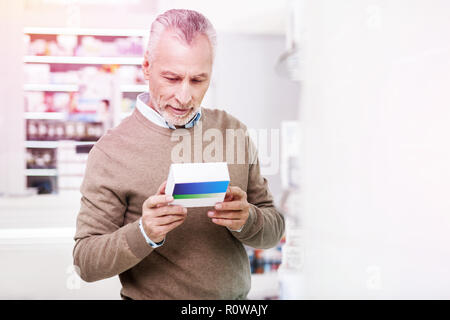 Indecisive grey-haired man reading details on a medication - Stock Photo