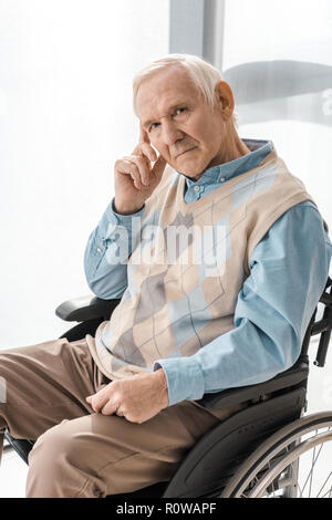 thoughtful sad senior man sitting in wheelchair in nursing home - Stock Photo