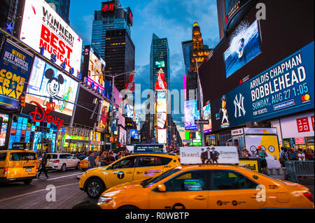 NEW YORK CITY - CIRCA AUGUST, 2018: Yellow taxis with on-board billboards compete for attention with the flashing signs of Times Square. - Stock Photo