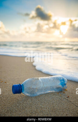 Plastic waste water bottle washed up in the waves on the shore of an empty tropical beach - Stock Photo