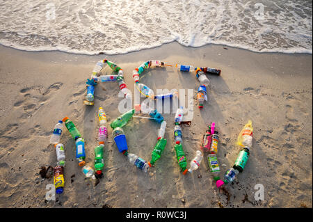MIAMI - CIRCA AUGUST, 2018: Ocean plastic pollution awareness message spelling out Act Now made from consumer drink bottles found on the beach - Stock Photo