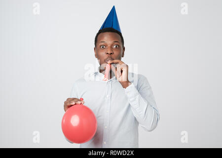 Young african man having fun on party wearing blue shirt and holiday hat, blowing party horn. - Stock Photo