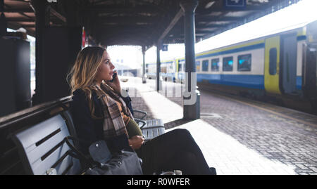 Pregnant woman talking on mobile phone at railway station - Stock Photo