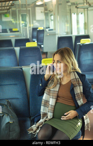 Pregnant woman talking on mobile phone while travelling in train - Stock Photo