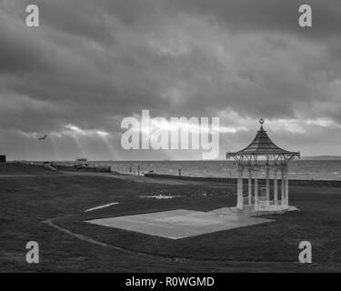 Stormy Southsea Beach with light rays over the bandstand in black and white, Southsea, Portsmouth, Hampshire, UK - Stock Photo
