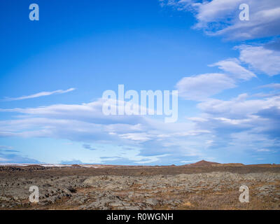 Typical Icelandic landscape with mountains top on horizon under blue cloudy sky - Stock Photo