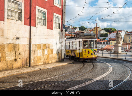 LISBON, PORTUGAL - July 1, 2018: Vintage tram in the narrow street of Alfama district in Lisbon. - Stock Photo