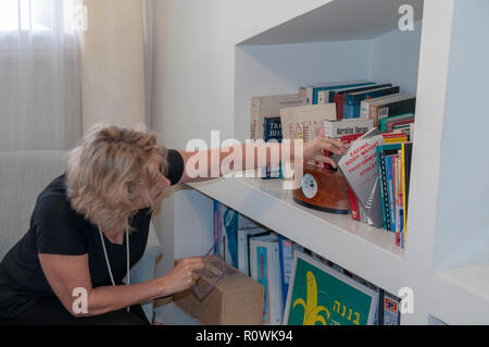 Female therapist is looking through her reference books on a bookshelf in a medical professional's consulting room. Model release Available - Stock Photo