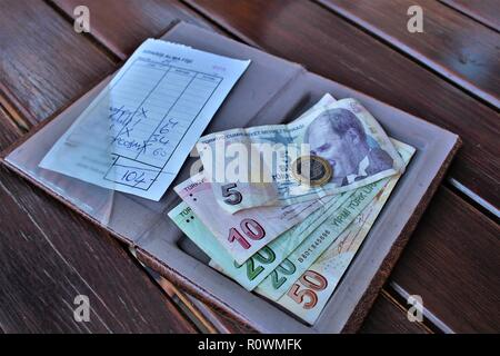 Dalyan, Turkey - July 7th 2018: Turkish Lira currency being used to pay a restaurant bill. - Stock Photo