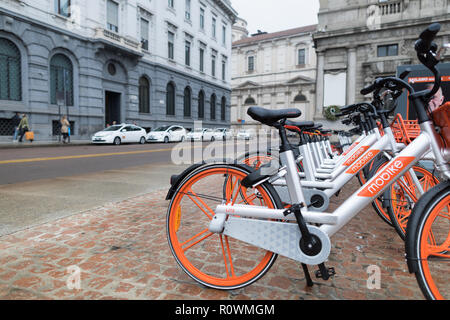 Milan, Italy - October 27, 2018: Piazza della Scala, rental bikes parked in a row on the square. The orange and silver bicycles are from Mobike, a com - Stock Photo
