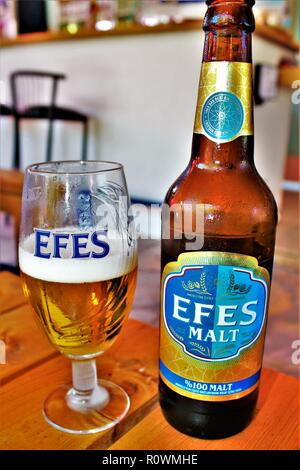 Dalyan, Turkey - July 9th 2018: A cool bottle of 'Efes Malt' lager is served up in a bar. Efes is the best-selling beer brand in Turkey. - Stock Photo