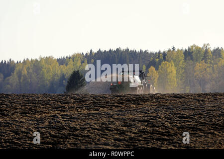 Salo, Finland - May 11, 2018: Farmer spreading manure on tilled field with tractor and spreader on a beautiful spring evening in South of Finland. - Stock Photo