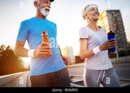 Senior woman and man running doing fitness exercises - Stock Photo