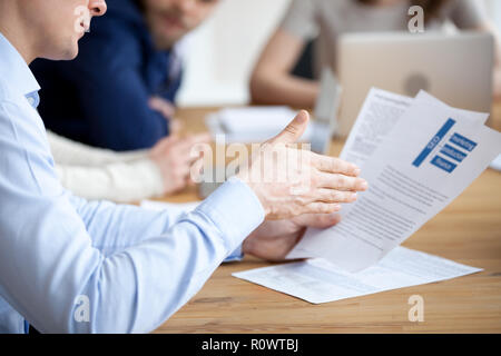 Close up of male employee reading paperwork report at meeting - Stock Photo