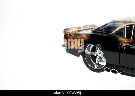 Rear view of a muscle diecast car double exposured with sunset clouds image on isolated white background - Stock Photo