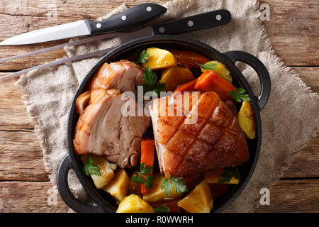 German recipe Krustenbraten crispy pork served with vegetables and gravy close-up in a pan on the table. horizontal top view from above - Stock Photo