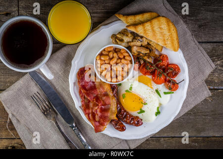Full english breakfast - eggs, bacon, beans, toast, coffee and juice - Stock Photo