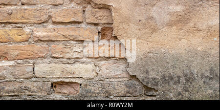 Old brick wall with peel stucco texture. Retro vintage worn wall background. Decayed cracked rough abstract wall surface