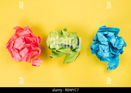 pink, blue and green crumpled paper balls on bright yellow background. concept of idea, recycle and stress - Stock Photo