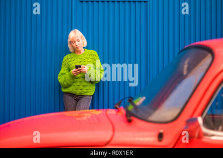 Colors and alternative happy lifestyle concept image with blonde attractive woman thirty years old using mobile phone internet technology outside the  - Stock Photo