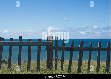 Pacific Ocean view from a grassy knoll behind a wooden barrier fence against a blue sky with puffy clouds - Stock Photo
