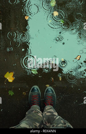 Standing in the drizzle puddle on the street, top view of sneakers in water - Stock Photo
