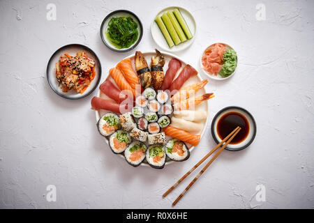 Various sushi rolls placed on round ceramic plate