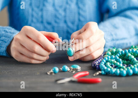 Person making jewelry using wire, chains and beads and other materials with craft tools - Stock Photo
