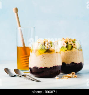 Vegan layered banana dessert of green buckwheat, chia seeds and quinoa with blueberry jam in a glass with fresh fruits, nuts and honey. healthy mornin - Stock Photo