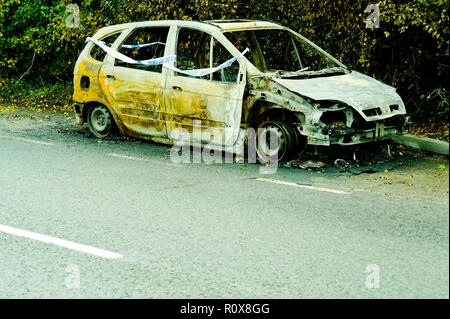Burnt out car on roadside with Police tape around it. - Stock Photo